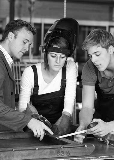 3 junge Menschen in Werkstatt als Symbol für Ausbildung